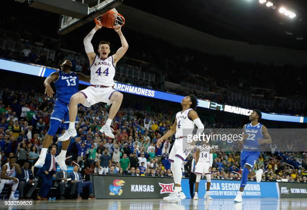 Mitch Lightfoot of the Kansas Jayhawks dunks against Myles Powell of the Seton Hall Pirates in the second half during the second round of the 2018...