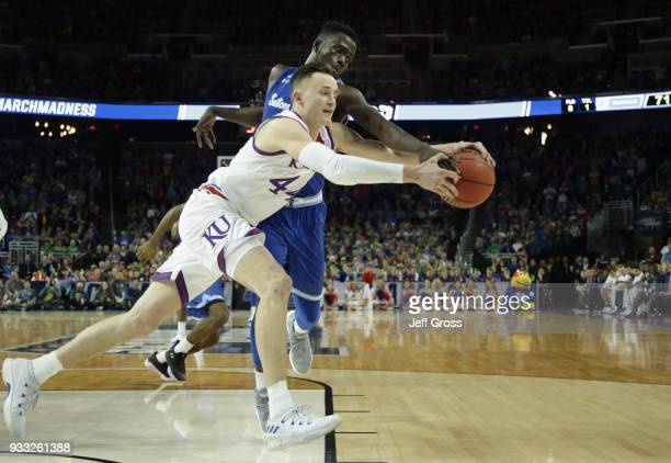 Mitch Lightfoot of the Kansas Jayhawks fights for the ball against Ismael Sanogo of the Seton Hall Pirates in the second half during the second round...