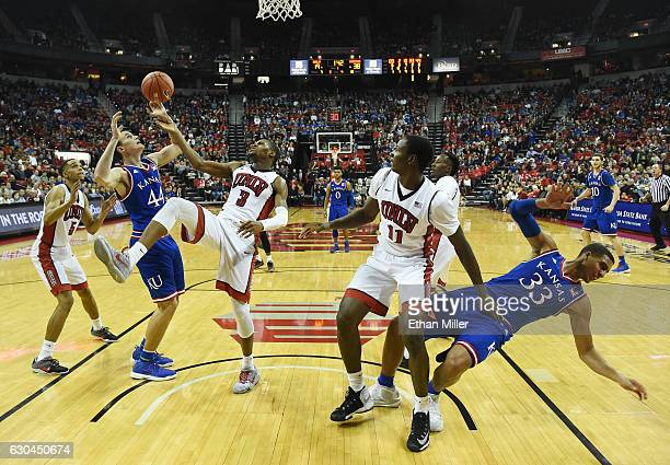 Mitch Lightfoot of the Kansas Jayhawks is fouled by Tyrell Green of the UNLV Rebels as they fight for a rebound after a shot by Landen Lucas of the...