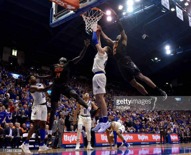 Mitch Lightfoot of the Kansas Jayhawks rebounds against Yor Anei and Cameron McGriff of the Oklahoma State Cowboys in the second half at Allen...