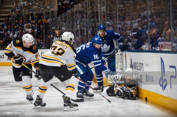 Mitch Marner of the Toronto Maple Leafs battles for the puck against Danton Heinen of the Boston Bruins during the third period during Game Six of...