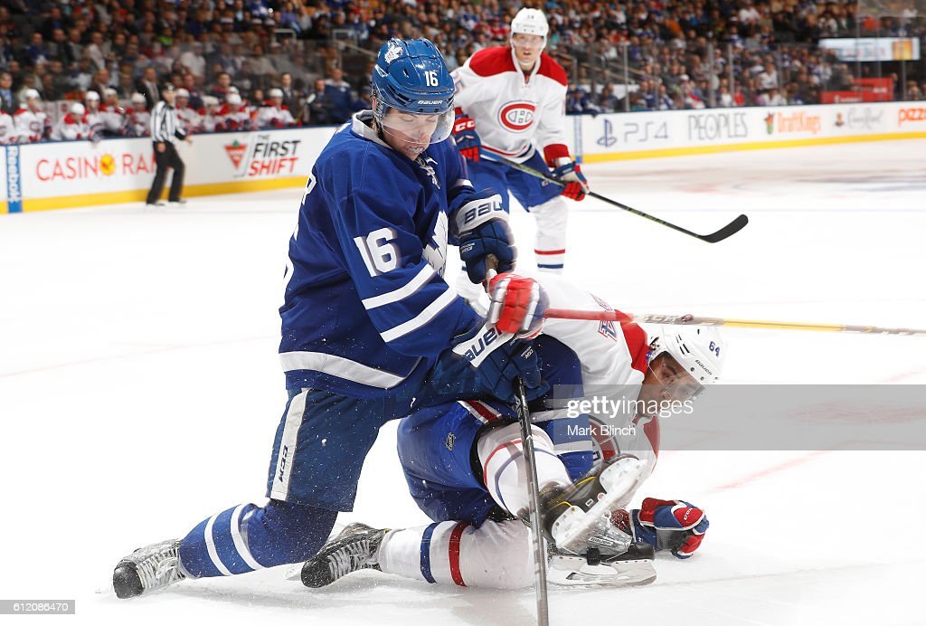 Mitch Marner #16 of the Toronto Maple Leafs battles for the puck with Jeremiah Addison #64 of the Montreal Canadiens during the third period of their NHL preseason game at the Air Canada Centre on October 2, 2016 in Toronto, ON, Canada.