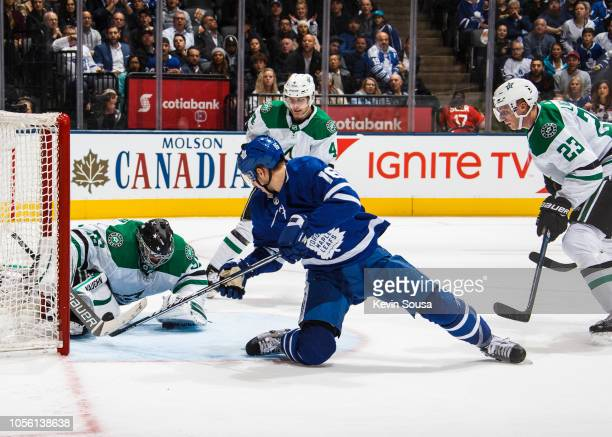 Mitch Marner of the Toronto Maple Leafs battles in front of the net against Anton Khudobin of the Dallas Stars and teammates Esa Lindell and Miro...