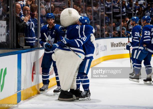 Mitch Marner of the Toronto Maple Leafs hugs mascot Carlton the Bear after defeating the Boston Bruins in Game Three of the Eastern Conference First...
