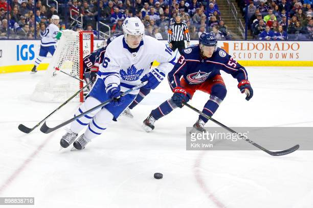 Mitch Marner of the Toronto Maple Leafs skates the puck away from Gabriel Carlsson of the Columbus Blue Jackets during the game on December 20 2017...