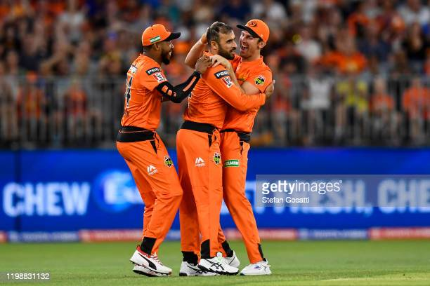 Mitch Marsh and Chris Jordan of the Scorchers congratulate Fawad Ahmed of the Scorchers after taking the wicket of Tom Banton of the Heat during the...