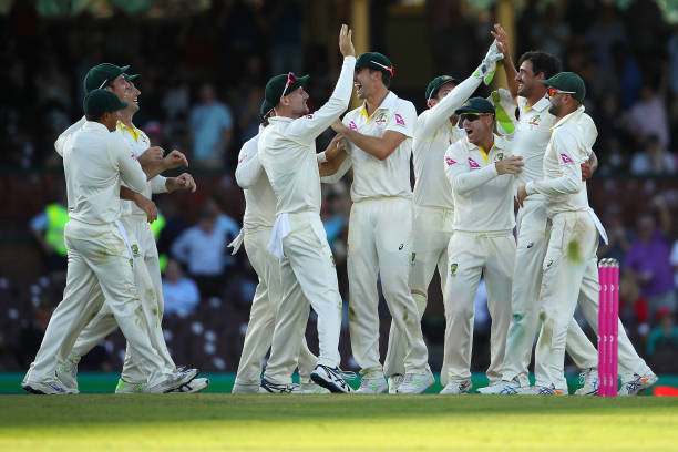 Mitch Marsh and Mitchell Starc of Australia celebrate with their team mates after combining to take the wicket of Joe Root of England during day one...