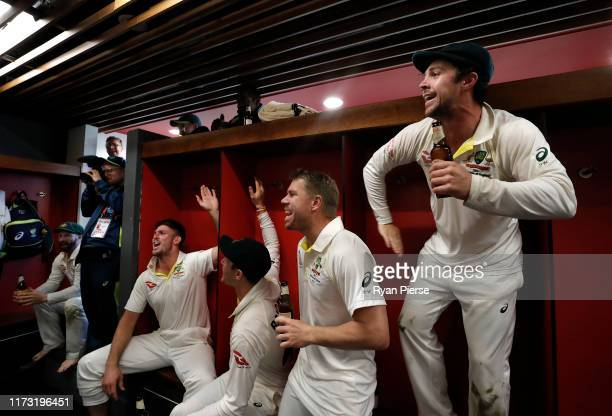 Mitch Marsh, David Warner and Travis Head of Australia celebrate in the change rooms after Australia claimed victory to retain the Ashes during day...