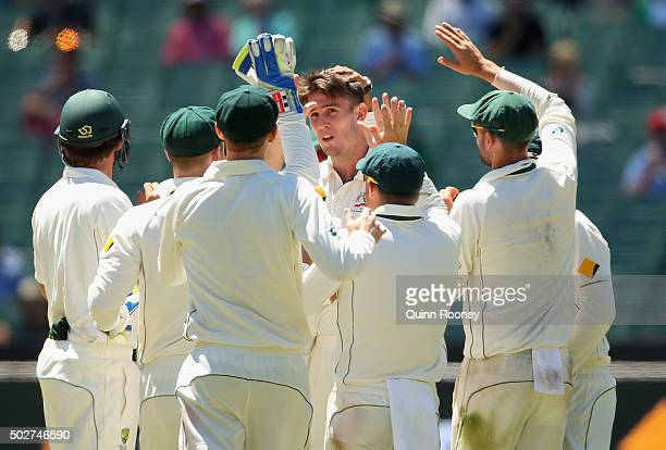Mitch Marsh of Australia is congratulated by team mates after getting the wicket of Marlon Samuels of the West Indies during day four of the Second...