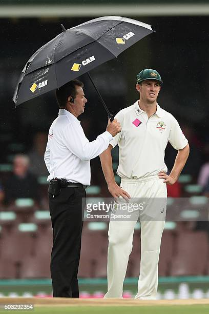 Mitch Marsh of Australia talks to an umpire as rain delays play during day two of the third Test match between Australia and the West Indies at...