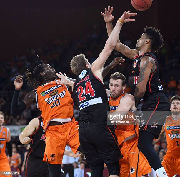 Mitch McCarron and Jerry Evans Jr of the Taipans contest the ball with Jesse Wagstaff and JeanPierre Tokoto of the Wildcats during the round 12 NBL...