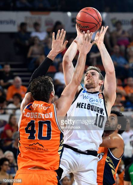 Mitch McCarron of Melbourne United takes a jump shot over Alex Loughton of the Taipans during the round four NBL match between the Cairns Taipans and...