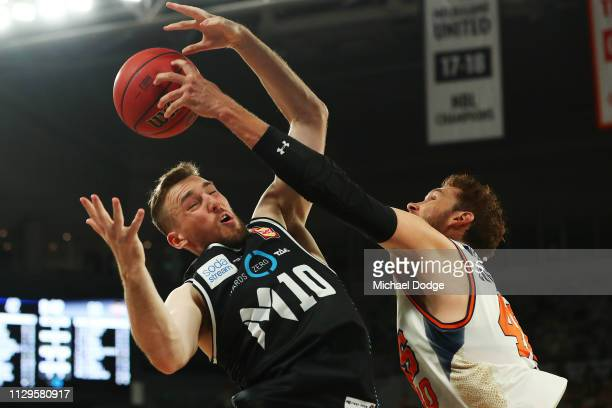 Mitch McCarron of United competes for the ball against Alex Loughton of the Taipans during the round 18 NBL match between Melbourne United and the...