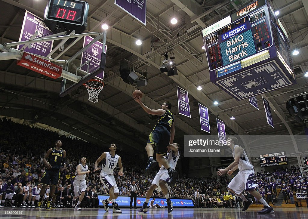 Mitch McGary #4 of the Michigan Wolverines puts up a shot over Jared Swopshire #12 and Mike Turner #10 of the Northwestern Wildcats at Welsh-Ryan Arena on January 3, 2013 in Evanston, Illinois. Michigan defeated Northwestern 94-66.