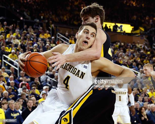 Mitch McGary of the Michigan Wolverines tries to get around the arm of Adam Woodbury of the Iowa Hawkeyes during the first half at Crisler Center on...