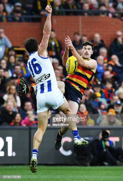Mitch McGovern of the Adelaide Crows attempts the mark but gets a free off Scott D Thompson of the Kangaroos during the round 22 AFL match between...