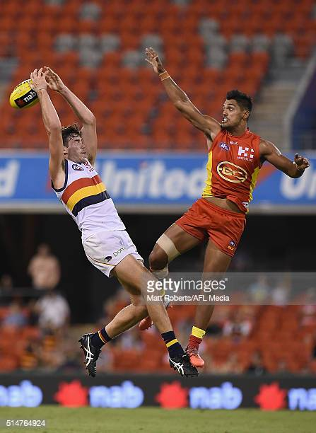 Mitch McGovern of the Crows competes for the ball against Aaron Hall of the Suns during the NAB Challenge AFL match between the Gold Coast Suns and...