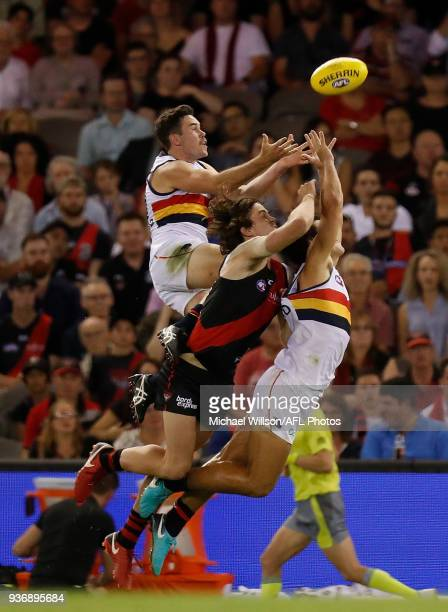 Mitch McGovern of the Crows Michael Hartley of the Bombers and Darcy Fogarty of the Crows compete for the ball during the 2018 AFL round 01 match...