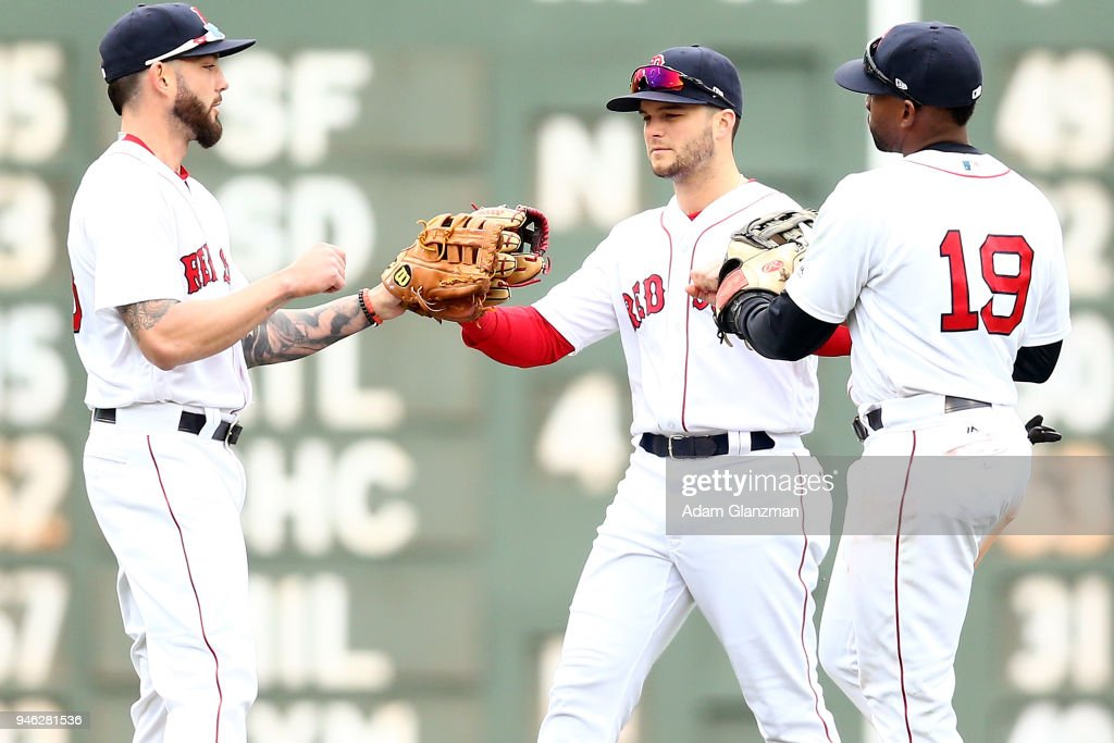 Mitch Moreland #18, Andrew Benintendi #16 and Jackie Bradley Jr. #19 of the Boston Red Sox embrace after a victory over the Baltimore Orioles at Fenway Park on April 14, 2018 in Boston, Massachusetts.
