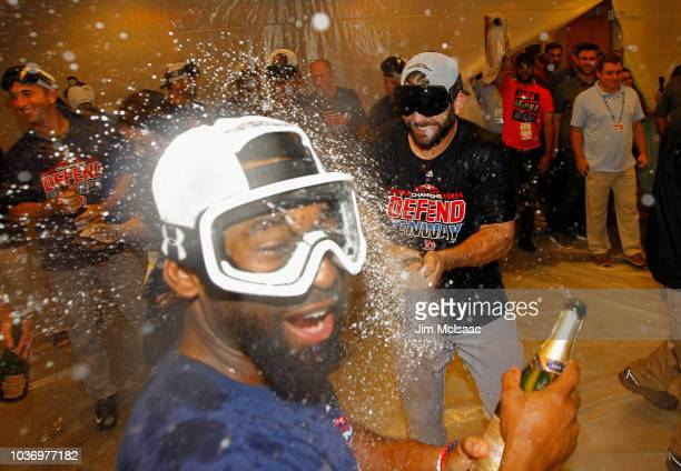 Mitch Moreland of the Boston Red Sox celebrates with teammate Jackie Bradley Jr #19 in the locker roon after defeating the New York Yankees to clinch...