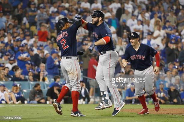 Mitch Moreland of the Boston Red Sox celebrates with Xander Bogaerts and Brock Holt after Moreland hit a threerun home run in the seventh inning...