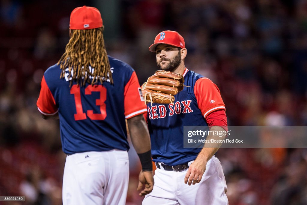 Mitch Moreland #18 of the Boston Red Sox high fives Hanley Ramirez #13 after pitching during the ninth inning of a game against the Baltimore Orioles on August 25, 2017 at Fenway Park in Boston, Massachusetts.