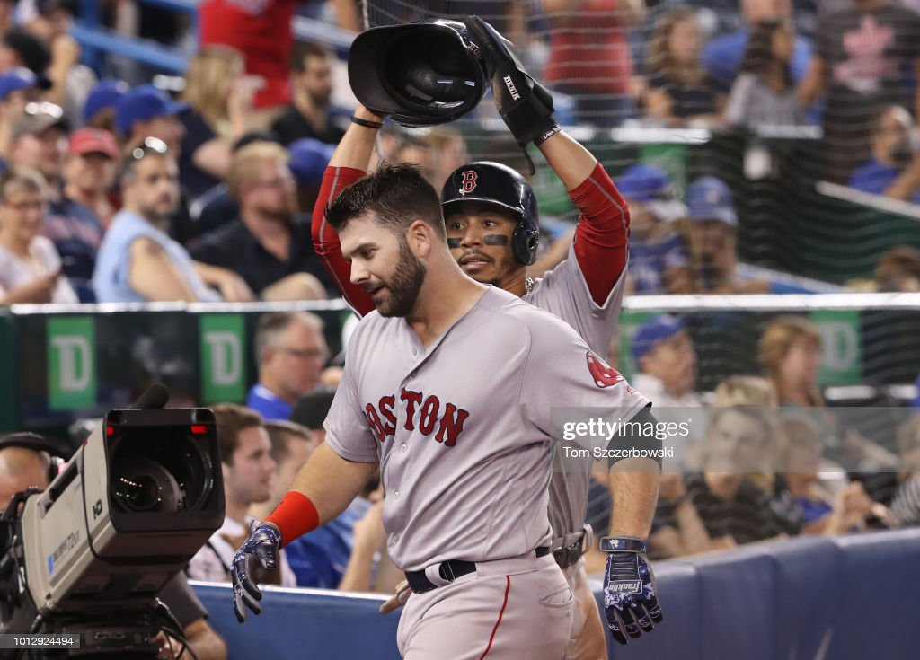 Mitch Moreland #18 of the Boston Red Sox is congratulated by Mookie Betts #50 after hitting a three-run home run in the 10th inning during MLB game action against the Toronto Blue Jays at Rogers Centre on August 7, 2018 in Toronto, Canada.