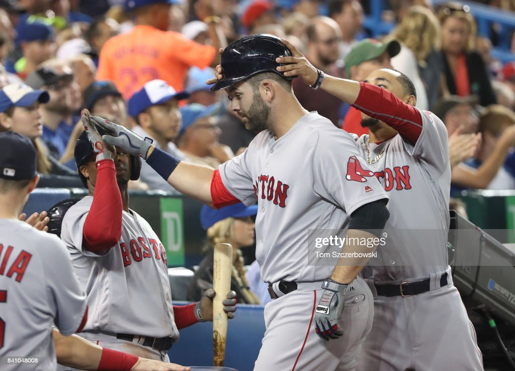 Mitch Moreland #18 of the Boston Red Sox is congratulated by Mookie Betts #50 and Rajai Davis #25 after hitting a two-run home run in the seventh inning during MLB game action against the Toronto Blue Jays at Rogers Centre on August 30, 2017 in Toronto, Canada.