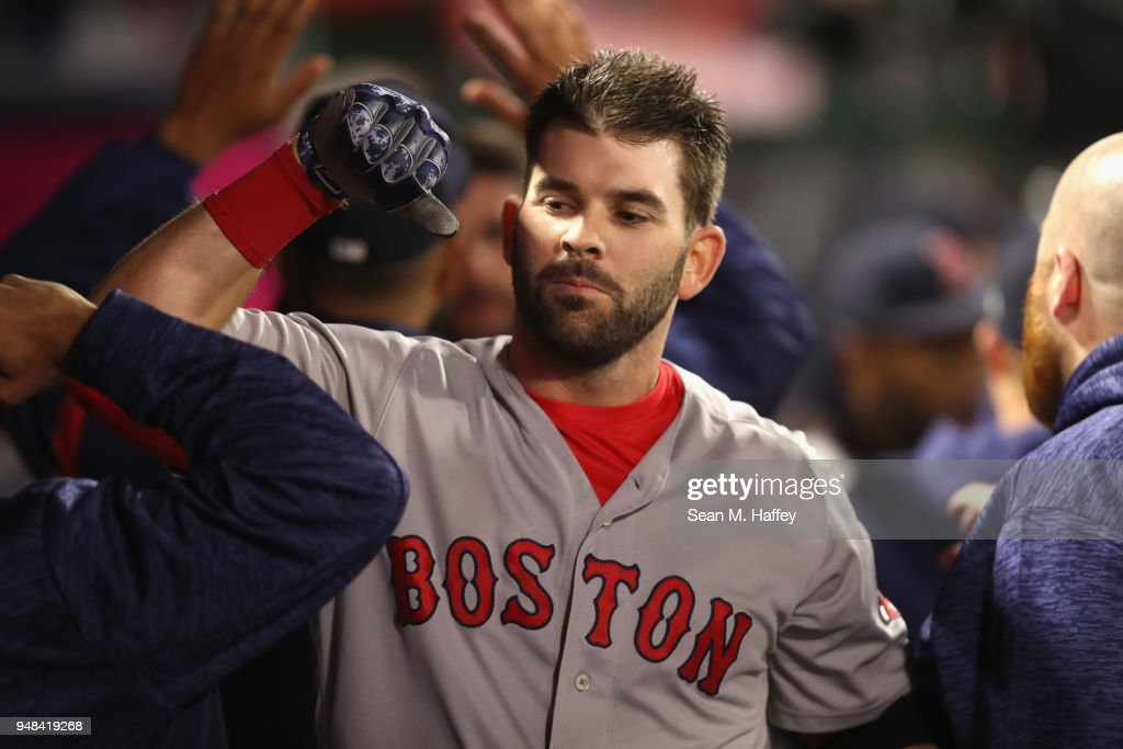Mitch Moreland #18 of the Boston Red Sox is congratulated in the dugout after hitting a two-run homerun during the ninth inning of a game against the Los Angeles Angels of Anaheim at Angel Stadium on April 18, 2018 in Anaheim, California.