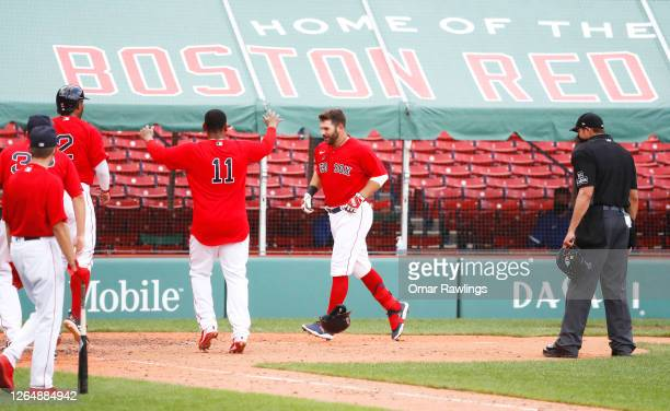 Mitch Moreland of the Boston Red Sox is mobbed at home plate after hitting a game winning home run in the bottom of the ninth inning against the...