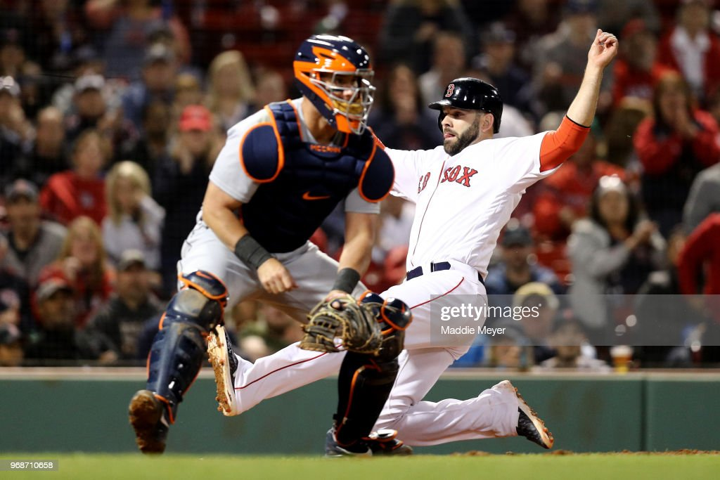 Mitch Moreland #18 of the Boston Red Sox slides past James McCann #34 of the Detroit Tigers to score a run during the eighth inning at Fenway Park on June 6, 2018 in Boston, Massachusetts.
