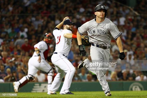 Mitch Moreland of the Boston Red Sox throws to first base while Shane Robinson of the New York Yankees runs to first base after bunting in the fifth...