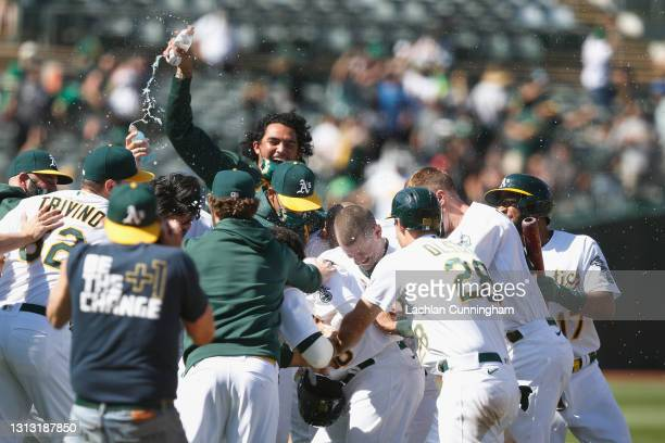 Mitch Moreland of the Oakland Athletics is mobbed by teammates after hitting into a fielding error to score teammate Matt Olson and win the game...