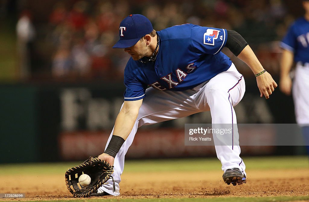 Mitch Moreland #18 of the Texas Rangers fields a ground ball down the first baseline for the out against the Seattle Mariners at Rangers Ballpark in Arlington on July 2, 2013 in Arlington, Texas.