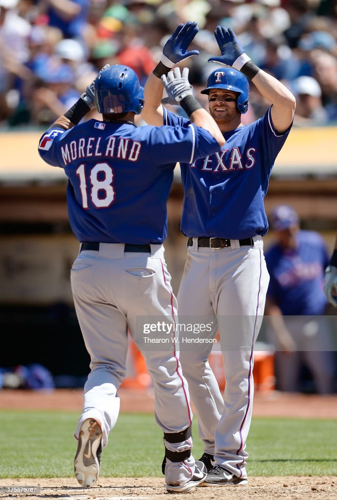 Mitch Moreland #18 of the Texas Rangers is congratulated by Craig Gentry #23 after Moreland hit a two-run homer in the seventh inning against the Oakland Athletics at O.co Coliseum on August 4, 2013 in Oakland, California.