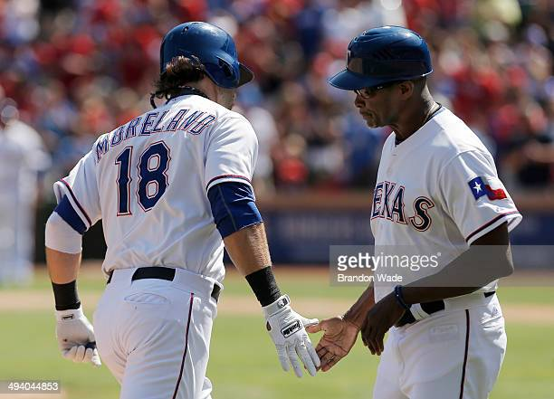 Mitch Moreland of the Texas Rangers is congratulated by third base coach Gary Pettis after hitting a home run during the seventh inning of a baseball...
