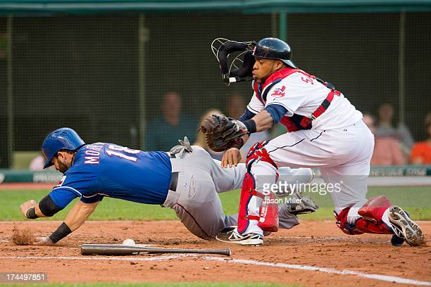 Mitch Moreland of the Texas Rangers scores on a sacrifice fly to left as catcher Carlos Santana of the Cleveland Indians drops the ball during the...