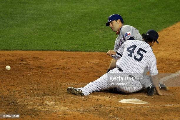 Mitch Moreland of the Texas Rangers scores on a wild pitch against Sergio Mitre of the New York Yankees in the top of the ninth inning of Game Three...