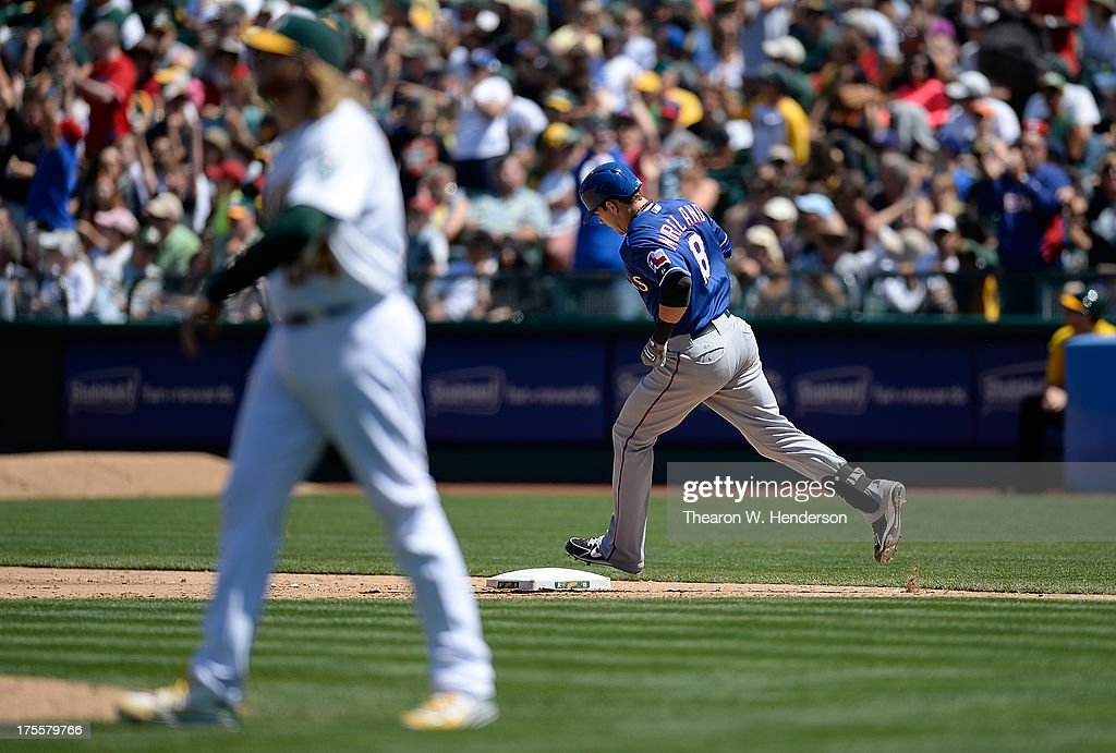 Mitch Moreland #18 of the Texas Rangers trots around the bases after hitting a two-run homer as pitcher A.J. Griffin #64 of the Oakland Athletics looks on in the seventh inning at O.co Coliseum on August 4, 2013 in Oakland, California.