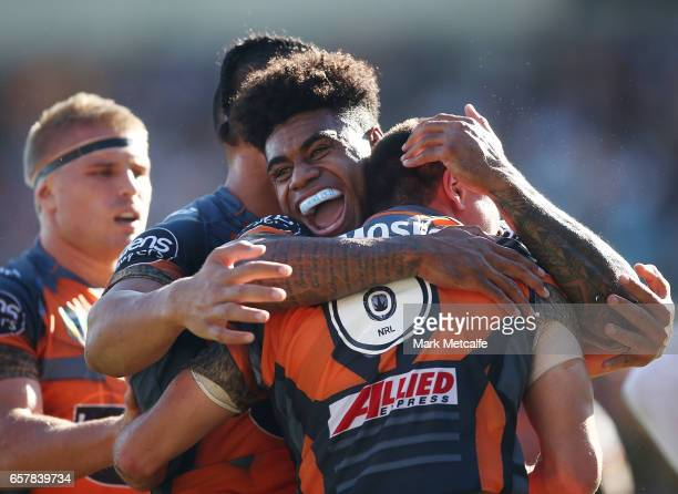 Mitch Moses of the Tigers celebrates scoring a try with team mate Kevin Naiqama of the Tigers during the round four NRL match between the Wests...