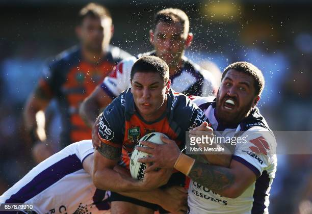 Mitch Moses of the Tigers is tackled during the round four NRL match between the Wests Tigers and the Melbourne Storm at Leichhardt Oval on March 26...