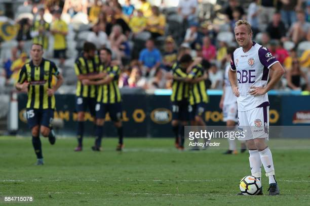 Mitch Nichols of Perth Glory is dejected at full time with Mariners celebrating in the background during the round nine ALeague match between the...