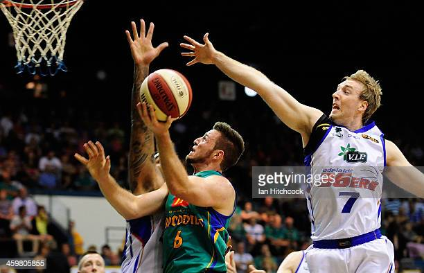 Mitch Norton of the Crocodiles drives to the basket past Brendan Teys of the 36ers during the round 11 NBL match between the Townsville Crocodiles...