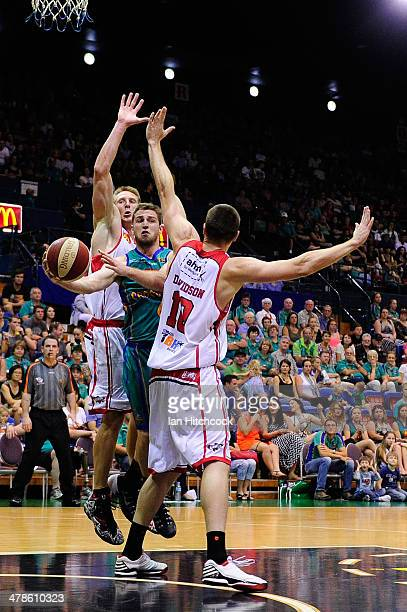 Mitch Norton of the Crocodiles gets a pass away in-between two hawks defenders during the round 22 NBL match between the Townsville Crocodiles and...