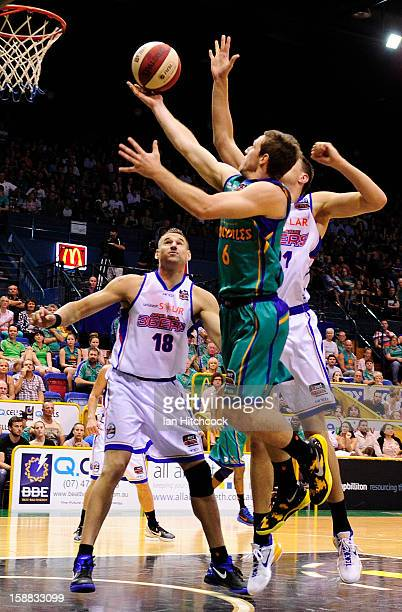 Mitch Norton of the Crocodiles goes for a layup past Pero Vasiljevic of the 36ers during the round 12 NBL match between the Townsville Crocodiles and...
