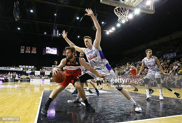 Mitch Norton of the Hawks is challenged by Matt Hodgson of the 36ers during the round 17 NBL match between the Illawarra Hawks and the Adelaide 36ers...