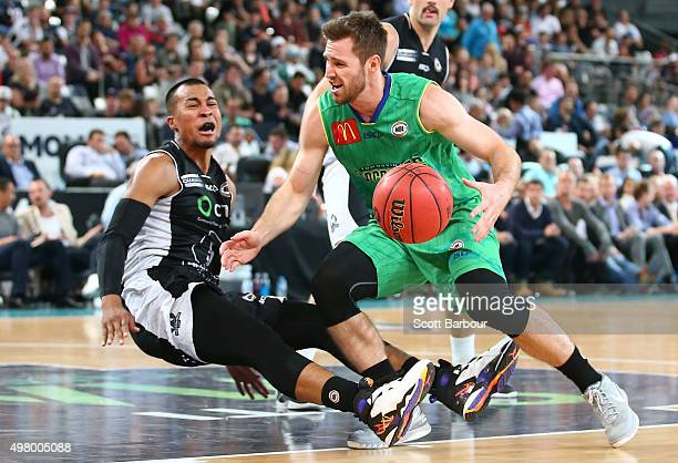 Mitch Norton of the Townsville Crocodiles drives to the basket as Stephen Holt of Melbourne United falls over and is called for a foul during the...