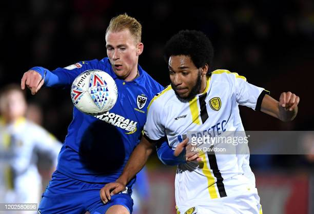 Mitch Pinnock of AFC Wimbledon battles for possession with Richard Nartey of Burton Albion during the Sky Bet League One match between AFC Wimbledon...