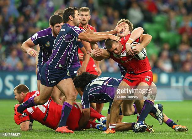 Mitch Rein of the Dragons is tackled by Cameron Smith and Tim Glasby of the Storm during the round 6 NRL match between the Melbourne Storm and the St...
