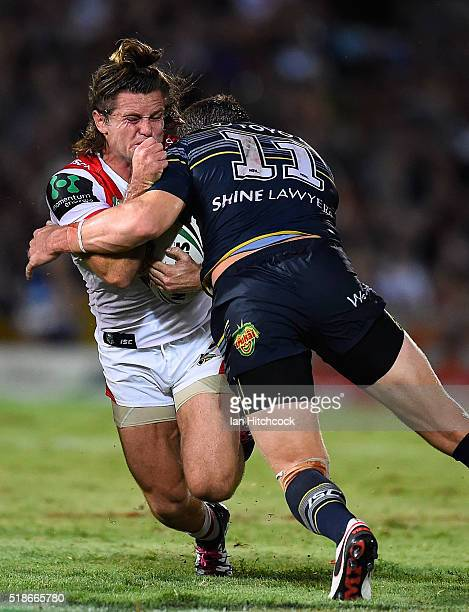 Mitch Rein of the Dragons is tackled by Gavin Cooper of the Cowboys during the round five NRL match between the North Queensland Cowboys and the St...